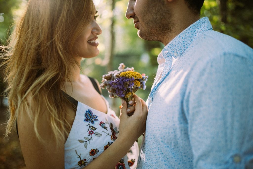 Beautiful couple giving flowers outside