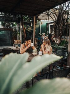 Couple on a coffee date outdoors with guy in green tank top