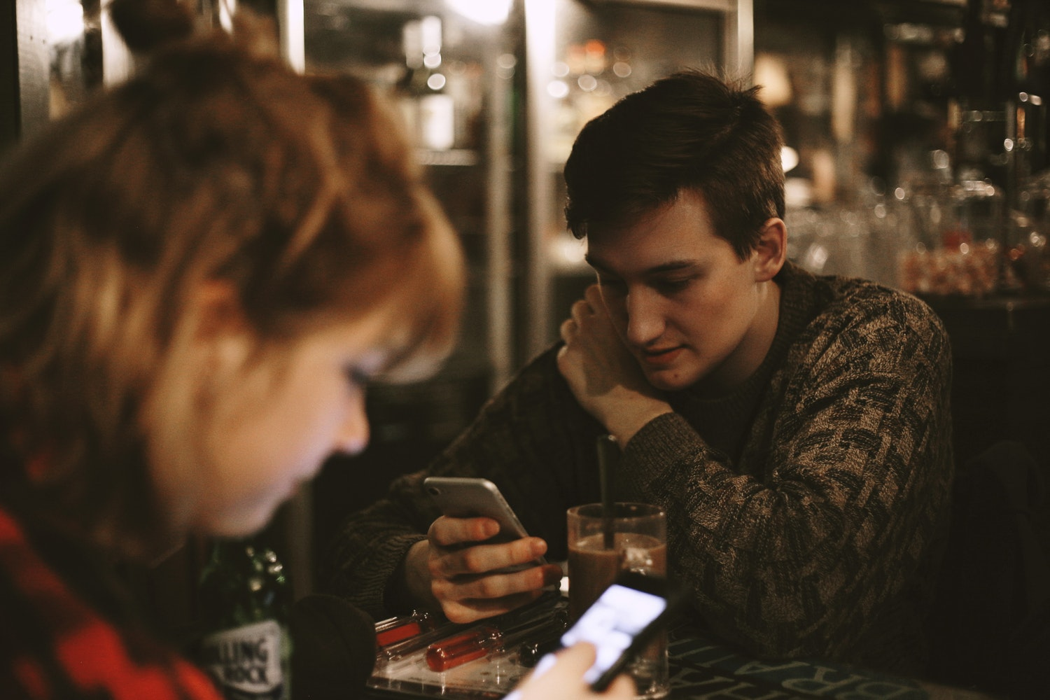 Man and Woman at a dark bar looking at their phones