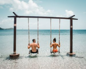 Couple on a swing on the Beach in the sea