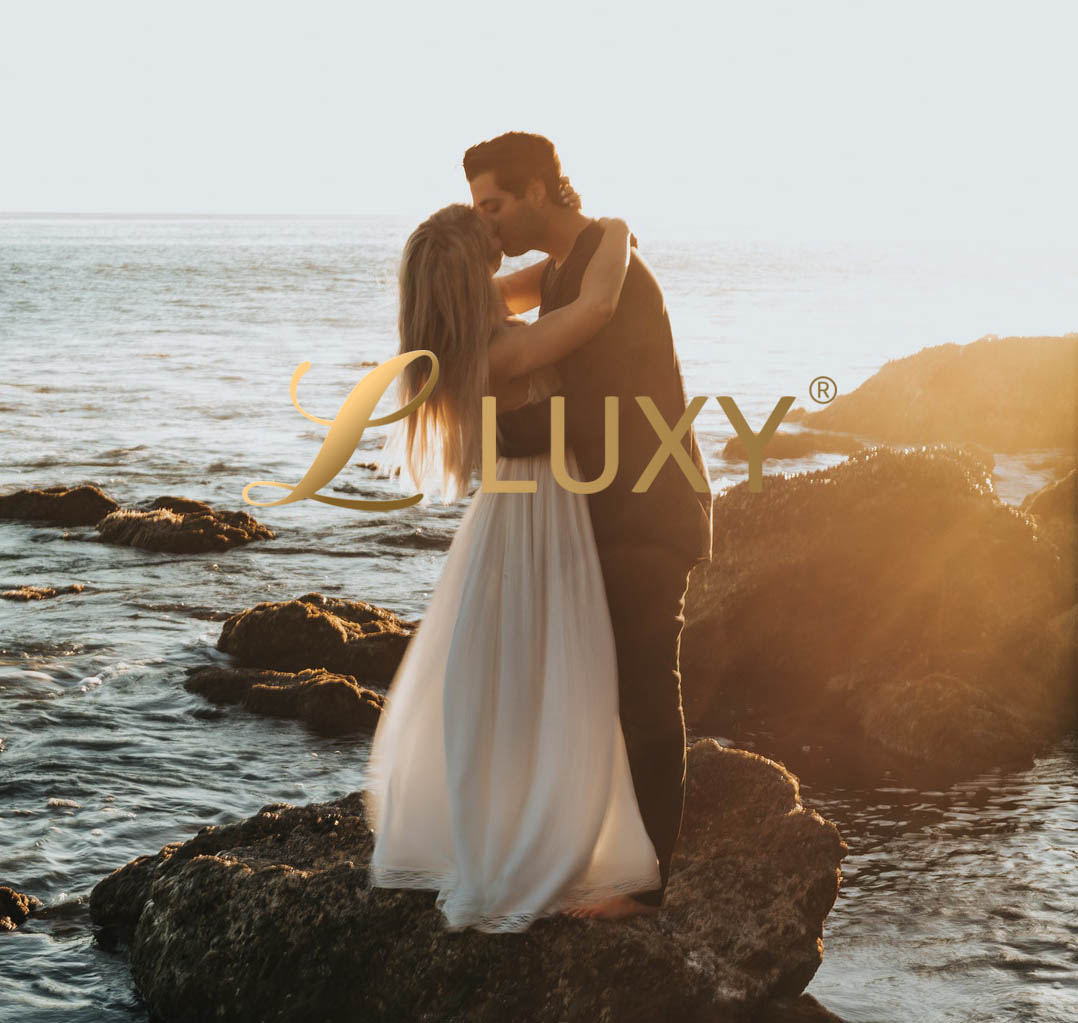 Couple kissing by the ocean at sunset