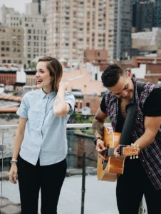 Guy playing the guitar and girl laughing while listening