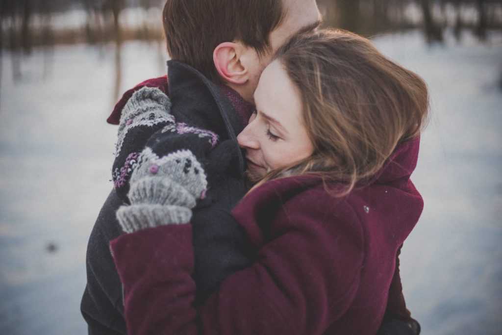 Cute winter couple hug in snow