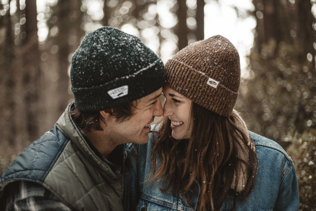 Cute winter couple snuggling in the snow