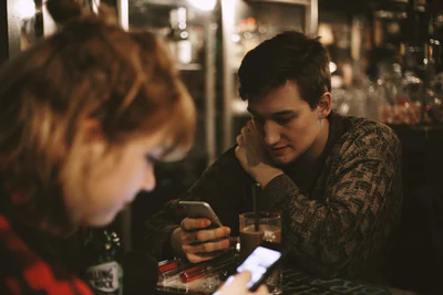 A couple at a bar focused on their phones