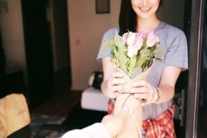 Giving a gift of flowers to a Smiling girl