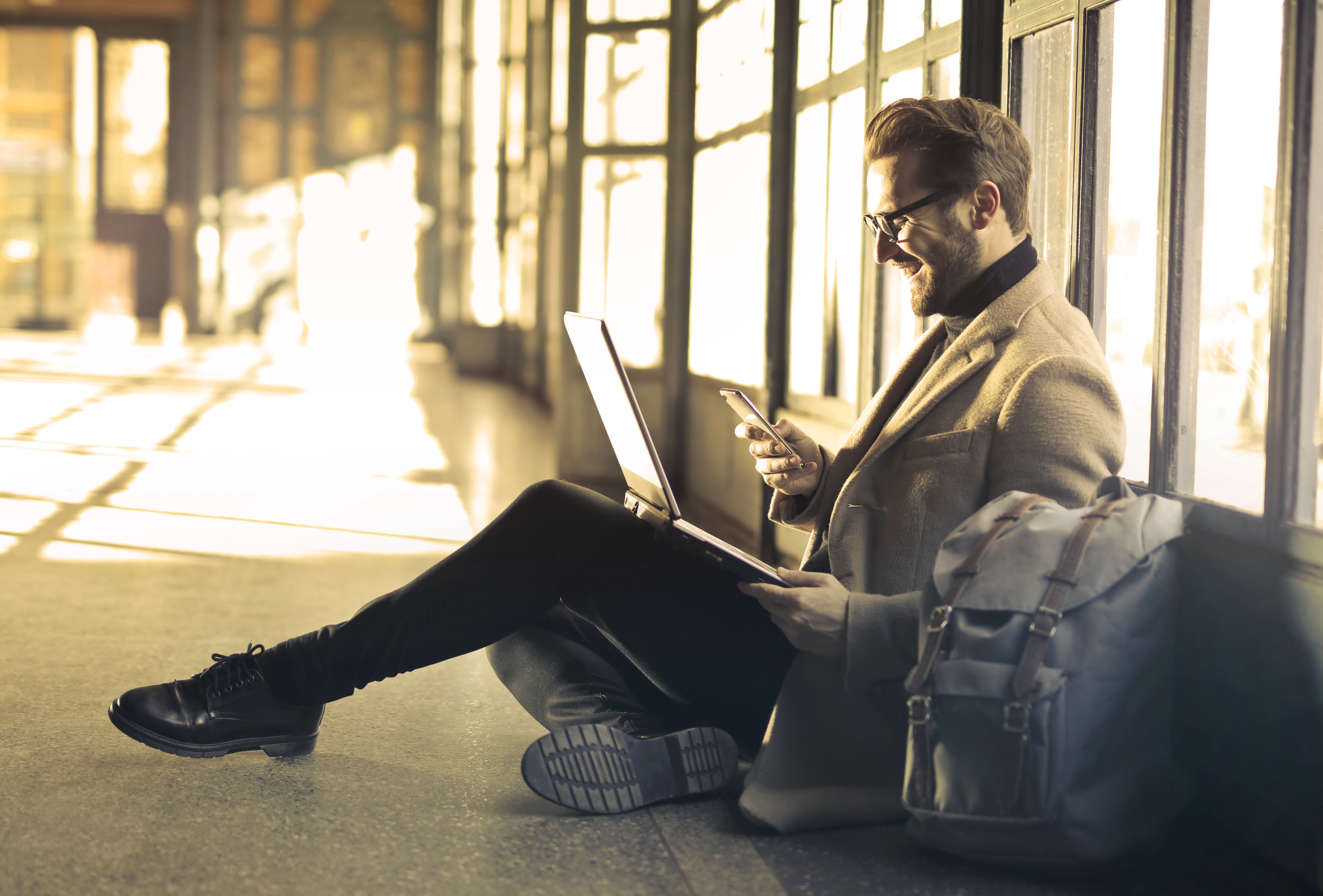 Good looking guy sitting on floor using phone and laptop