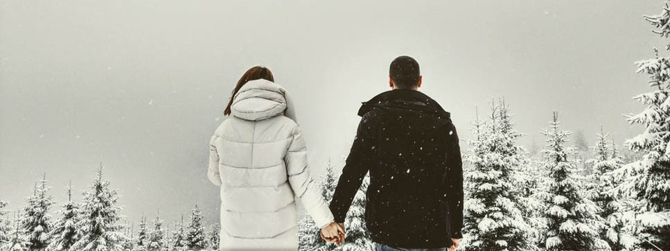 Couple Wrapped up Holding hands in the Winter snow