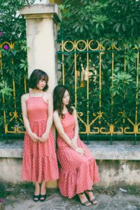 2 Women wearing matching red polka dot dresses