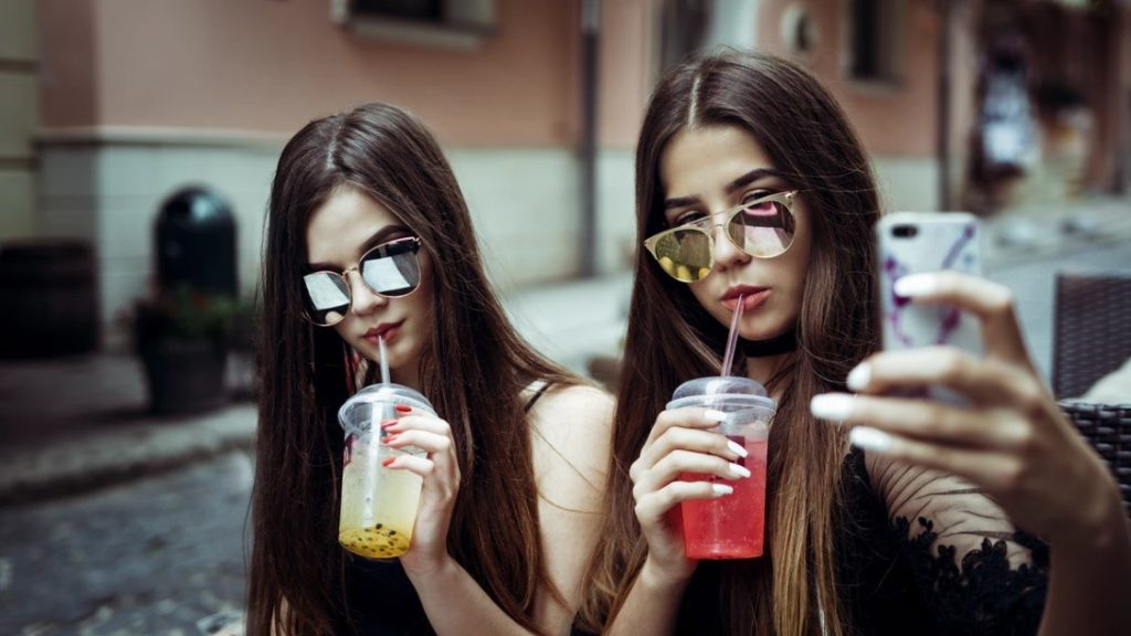 2 European Brunettes With Cold Drinks and Wearing Sunglasses Taking a Selfie Outside
