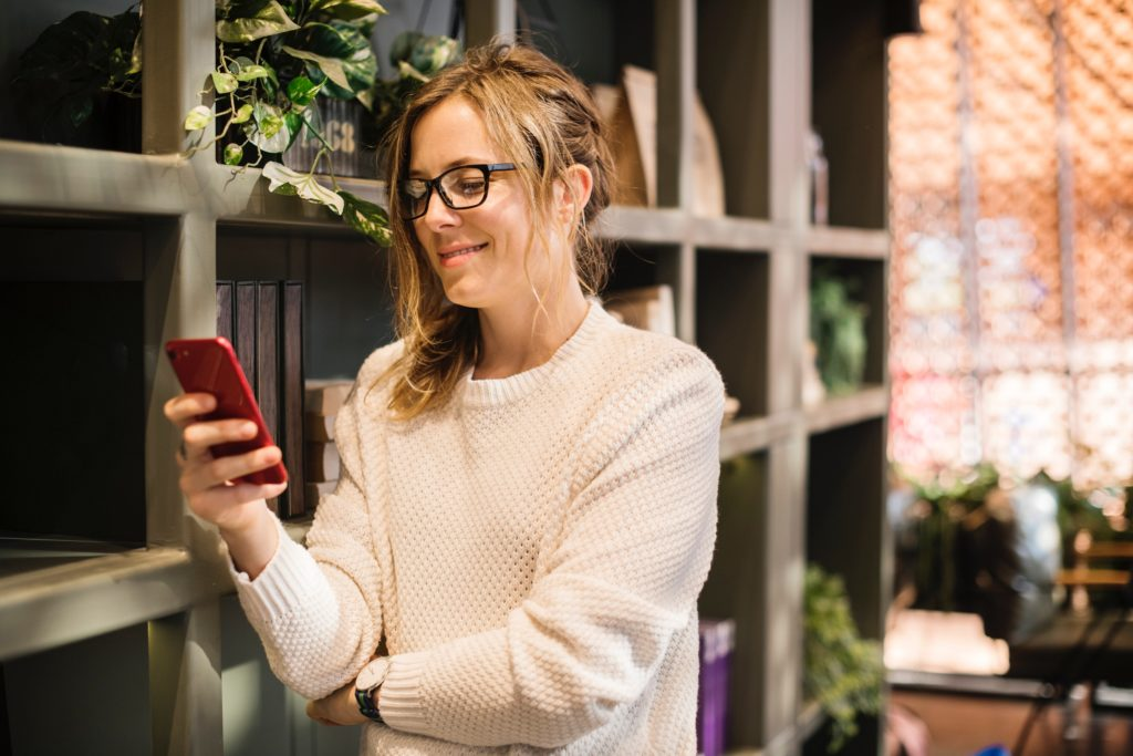 Smart woman checking iPhone by shelf