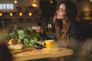 Woman eating a little of pasta food in a cafe