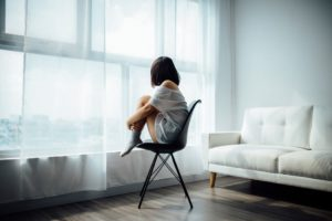 Woman sitting in chair in Tshirt and Socks looking out of window waiting
