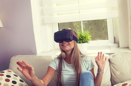 Beautiful blonde haired woman using VR while sat on a beige couch
