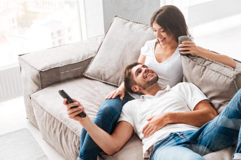 Romantic couple goals: New couple cuddling on the sofa