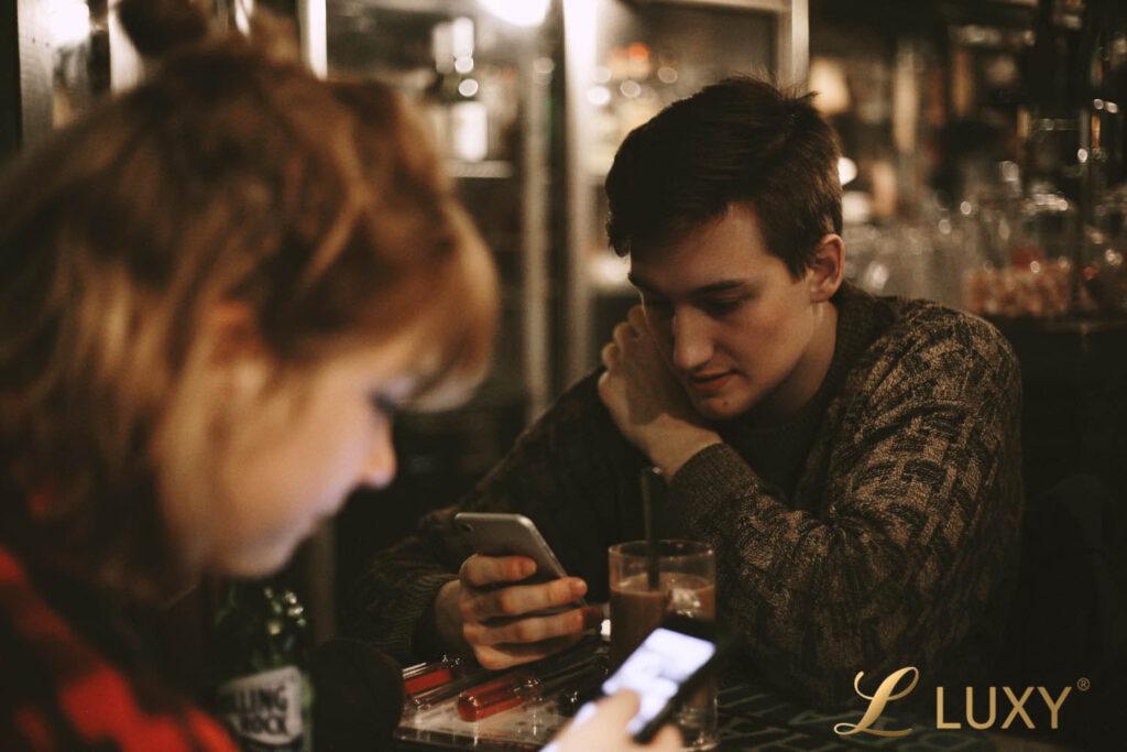 Couple at Bar looking at phones