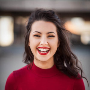 woman smiling in red top and red lipstick