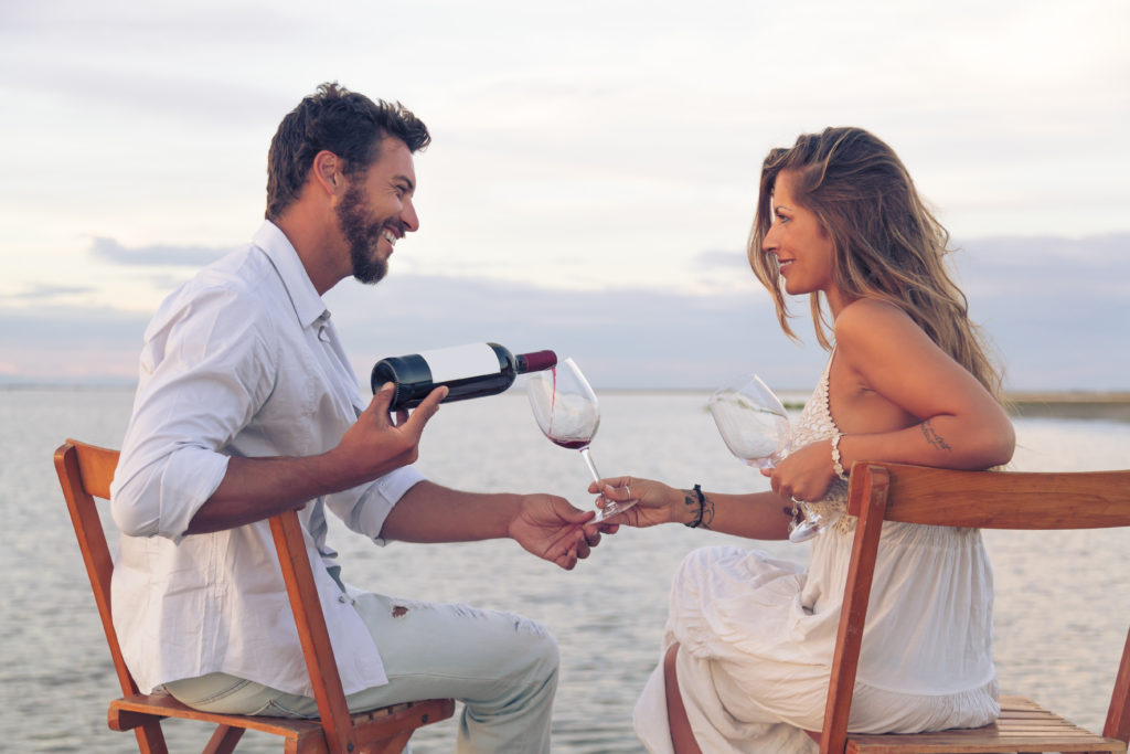 couple exclusive dating on a beach. Having wine for elite dating
