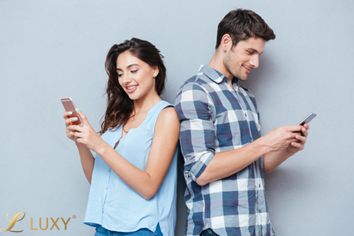 A woman and man texting and smiling.